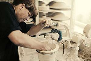 Katy West using the Jigger and Jolly machine at Highland Stoneware